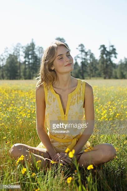 Young woman with eyes closed sitting in a field of wildflowers