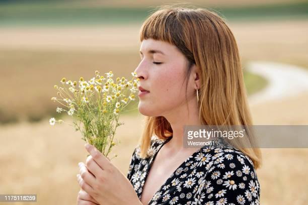 young woman with eyes closed smelling bunch of chamomile flower - natürliche schönheit personen stock-fotos und bilder