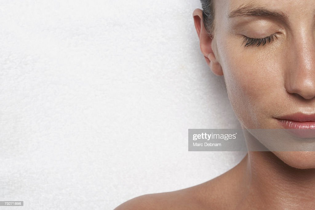 Young woman with eyes closed, smiling, close-up : Stock Photo