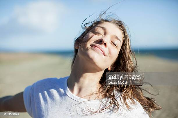 young woman with eyes closed smiling on a beach - alegre fotografías e imágenes de stock