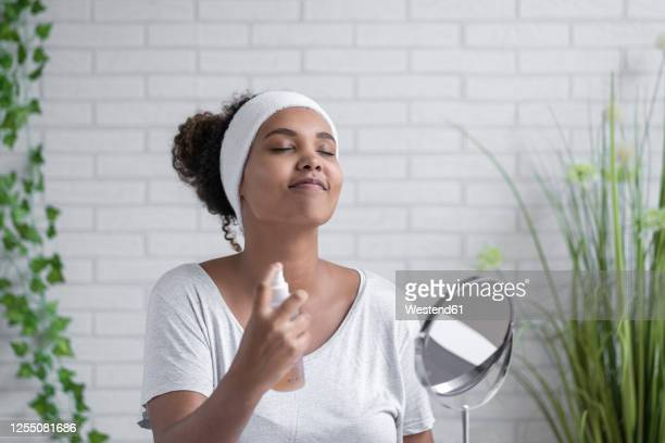 young woman with eyes closed spraying facial mist at home - spraying stock pictures, royalty-free photos & images