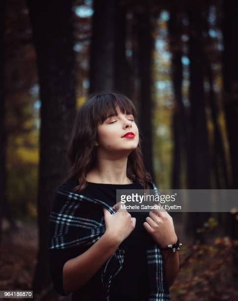 Young Woman With Eyes Closed Standing In Forest