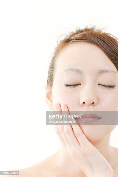 Young Woman with Eyes Closed Touching Her Face