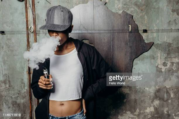young woman with eyes concealed by peak cap and midriff blowing out a thick puff vaping smoke africa motif on wall behind - thick black woman stock photos and pictures