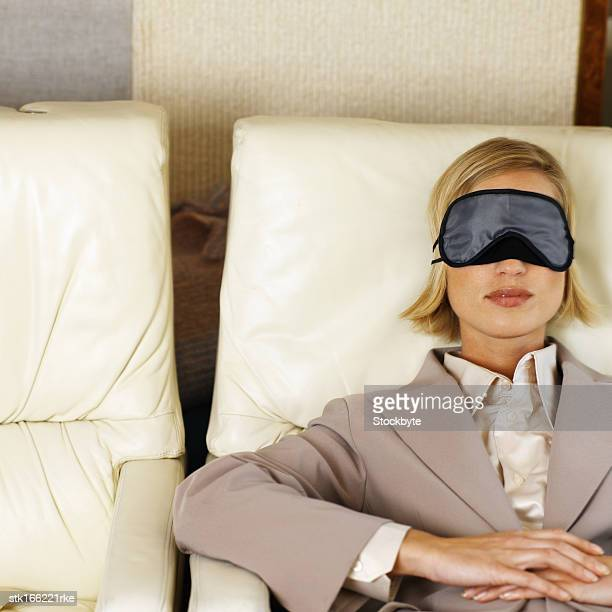young woman with eyes covered in an airplane