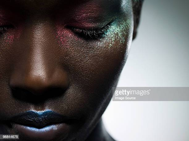 Young woman with face covered in metallic make up