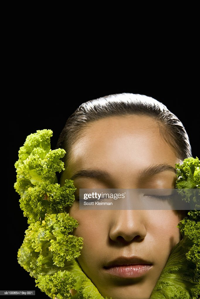 Young woman with face in kale leaves, eyes closed : Foto stock