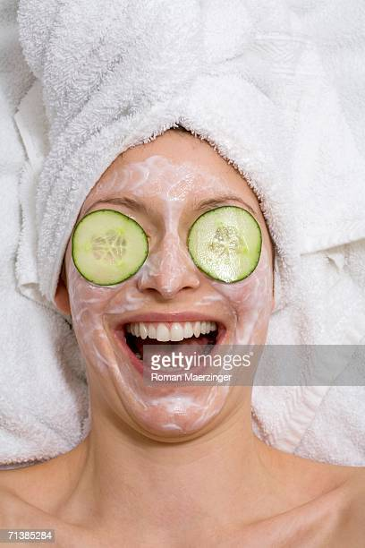 Young woman with face mask and cucumber slices, laughing, close-up
