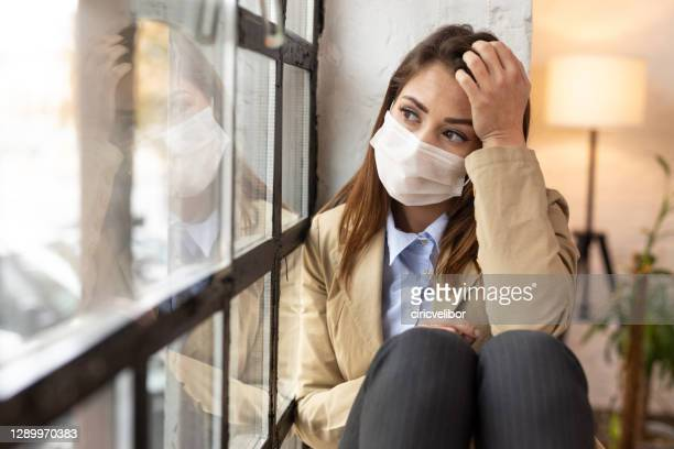 young woman with face mask feeling worried while sitting at home during virus epidemic - stay at home order stock pictures, royalty-free photos & images