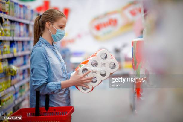 young woman with face mask holding and looking at toilet paper pack in store - kitchen paper stock pictures, royalty-free photos & images