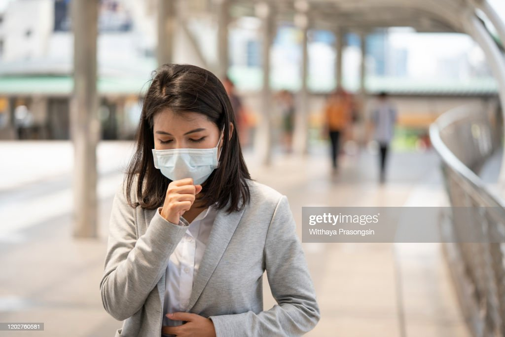 Young woman with face mask in the street : Stock Photo