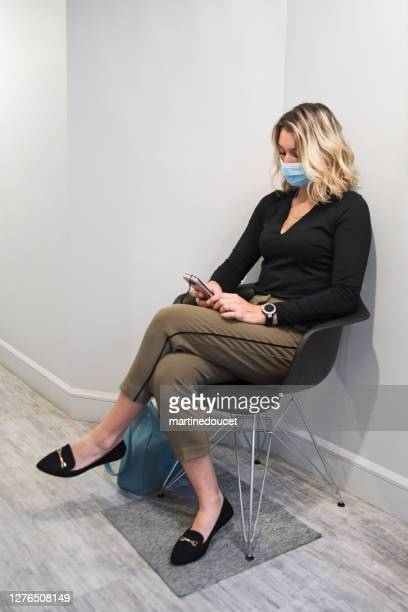 """young woman with face mask sitting in waiting room. - """"martine doucet"""" or martinedoucet stock pictures, royalty-free photos & images"""