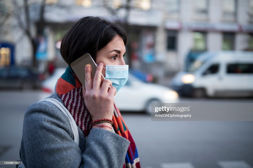 Young Woman With Face Mask Talking On The Phone. : Stock Photo