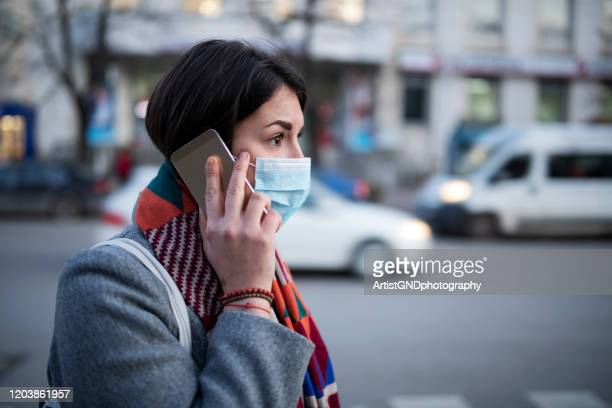 young woman with face mask talking on the phone. - coronavirus stock pictures, royalty-free photos & images