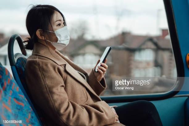 young woman with face mask using smartphone on public transport - window stock pictures, royalty-free photos & images