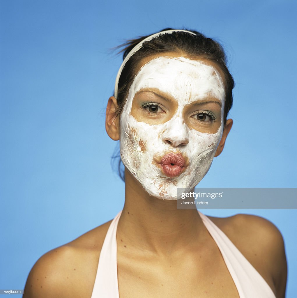 Young woman with face pack puckering lips : Stock Photo