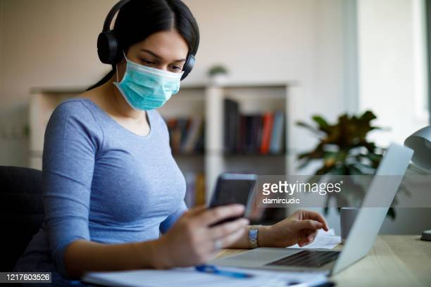 young woman with face protective mask working from home - prevention stock pictures, royalty-free photos & images