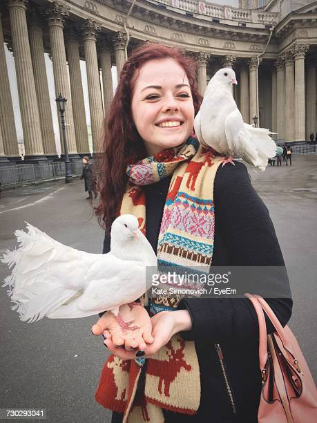 young woman with fantail pigeons perching on her hands while standing against kazan cathedral - teen russia stock photos and pictures