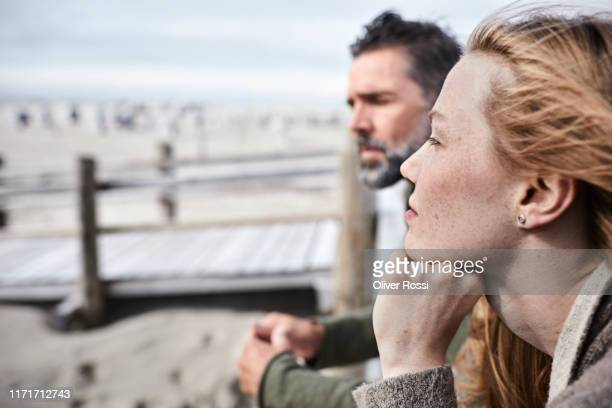 young woman with father on the beach looking at view - introspektion stock-fotos und bilder