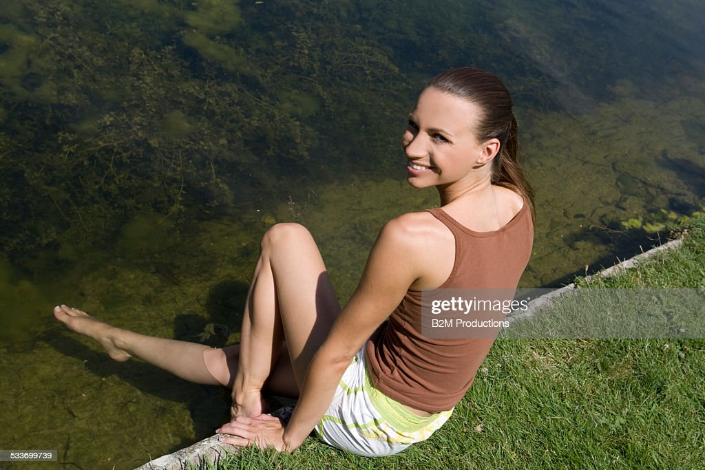 Young woman with feet on water : Foto stock