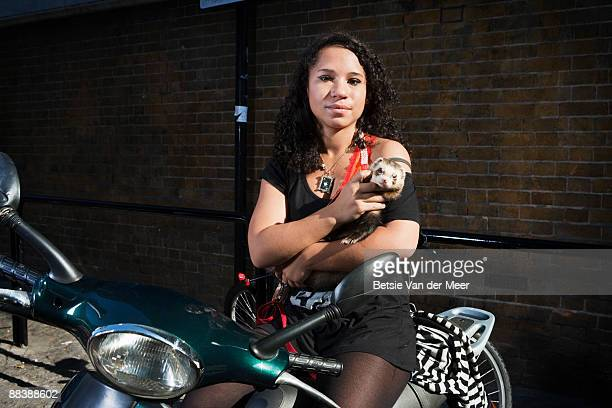 Young woman with ferret sitting on scooter.
