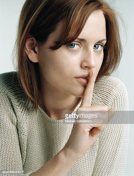 Young woman with finger in front of lips, close-up