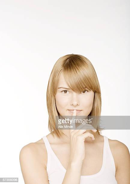 Young woman with finger in front of lips