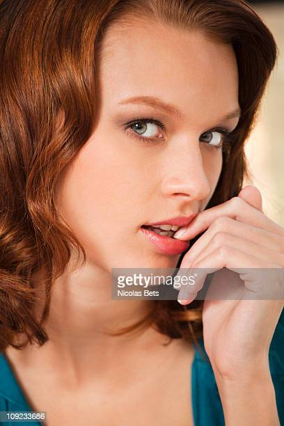Young woman with finger in mouth