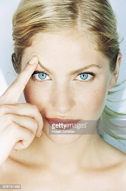 Young woman with finger on her eyebrow
