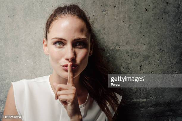young woman with finger on lips against wall - finger on lips stock pictures, royalty-free photos & images