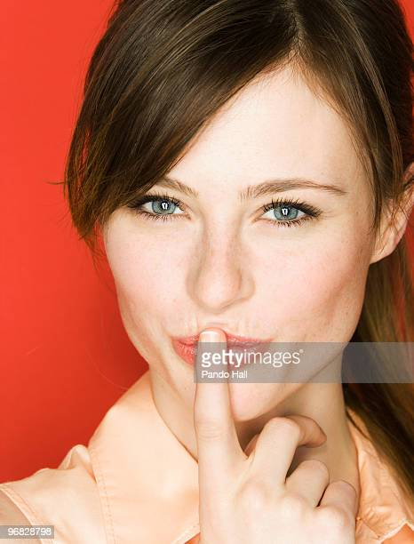 Young woman with finger on lips, smiling