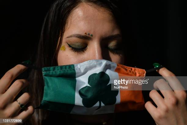 Young woman with fingernails and face decorated for St. Patrick's puts a face mask outside the Irish Potato Cake Company restaurant in Dublin's city...