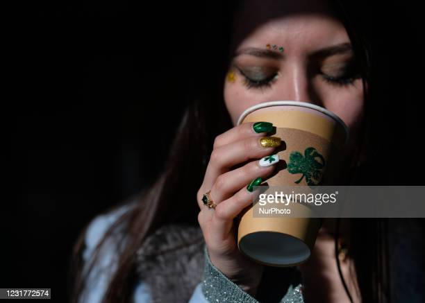 Young woman with fingernails decorated for St. Patrick's having a coffee outside the Irish Potato Cake Company restaurant in Dublin's city center on...