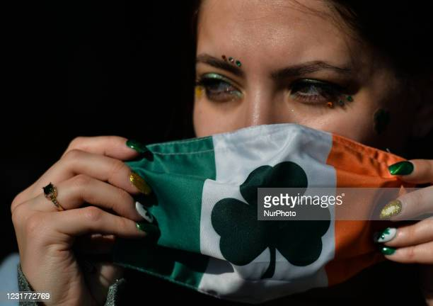 Young woman with fingernails decorated for St. Patrick's puts a face mask outside the Irish Potato Cake Company restaurant in Dublin's city center on...
