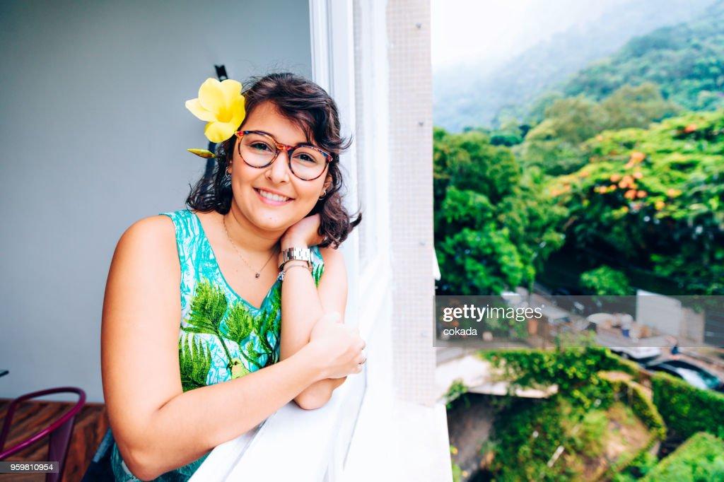 Junge Frau mit Blumen auf ihr ihr am Fenster : Stock-Foto