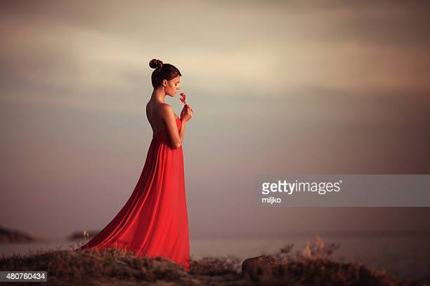 Young woman with flower standing by the sea at sunset