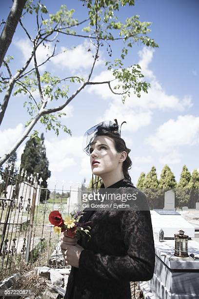 young woman with flowers in hand looking up - 埋葬地 ストックフォトと画像
