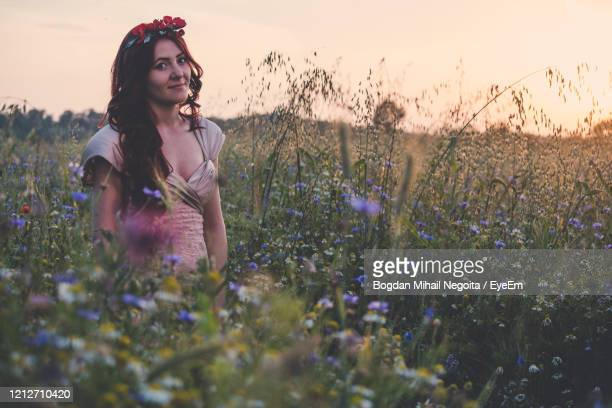 young woman with flowers on field against sky - bogdan negoita stock pictures, royalty-free photos & images
