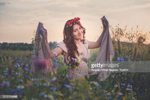 young woman with flowers on field - bogdan negoita stock pictures, royalty-free photos & images