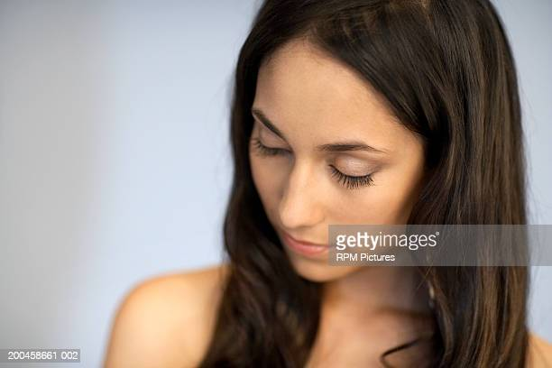 Young woman with flowing dark hair, eyes closed