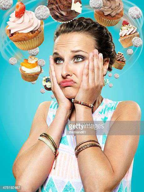 Young woman with flying cupcakes around her head, Composite
