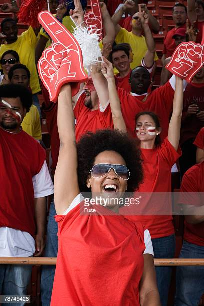 young woman with foam finger cheering - foam finger stock photos and pictures