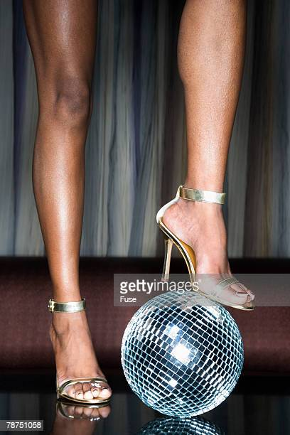 young woman with foot on disco ball - african american 70s fashion stock photos and pictures