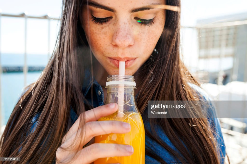 Young woman with freckles drinking orange juice : Stockfoto