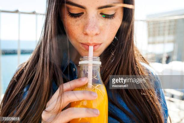 young woman with freckles drinking orange juice - zuid europese etniciteit stockfoto's en -beelden