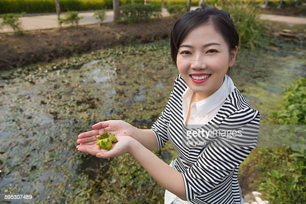 young woman with fresh picked water caltrops - trapa stock pictures, royalty-free photos & images