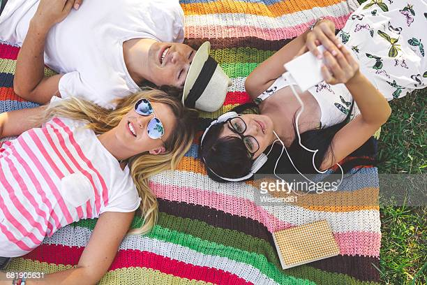 Young woman with friends lying on blanket listening to music
