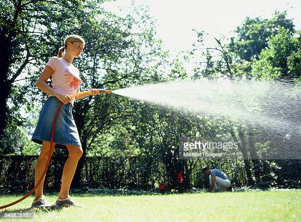 Young woman with garden hose