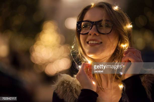 Young woman with garland of lights around her face