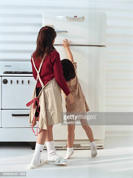 Young woman with girl (4-5) standing in front of refrigerator, rear view